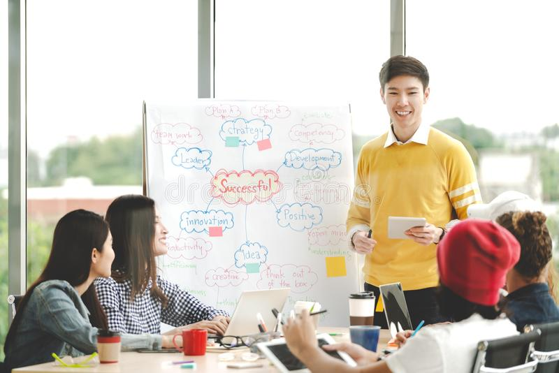 Young asian creative businessman standing and making presentation at modern office happy talking and brainstorming with teamwork b stock image