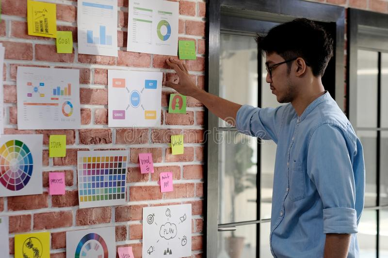 Young asian creative man reading and thinking about paper work ideas on office wall with concentration, Working  asian man reading royalty free stock photos