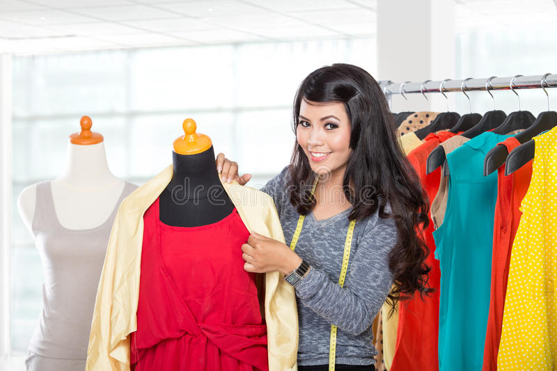 Young asian designer hold fabric enrobing it to the mannequin, s royalty free stock photography