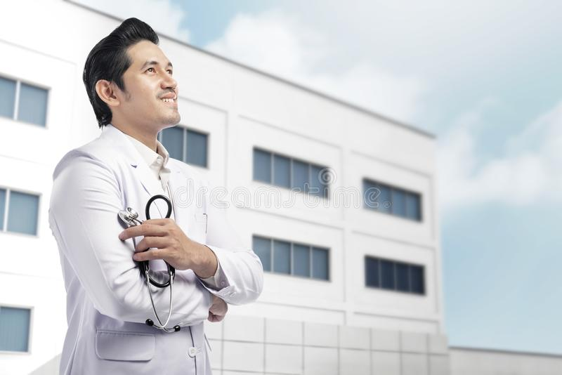 Young asian doctor man with white lab coat holding stethoscope w stock image