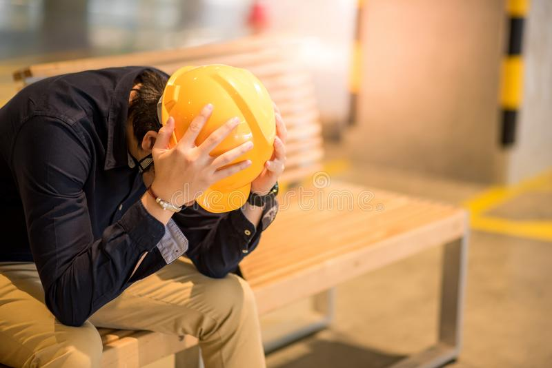 Young Asian engineer man feeling tried while sitting on bench. Young Asian engineer or architect man feeling tried and worried while sitting on bench holding his stock photo
