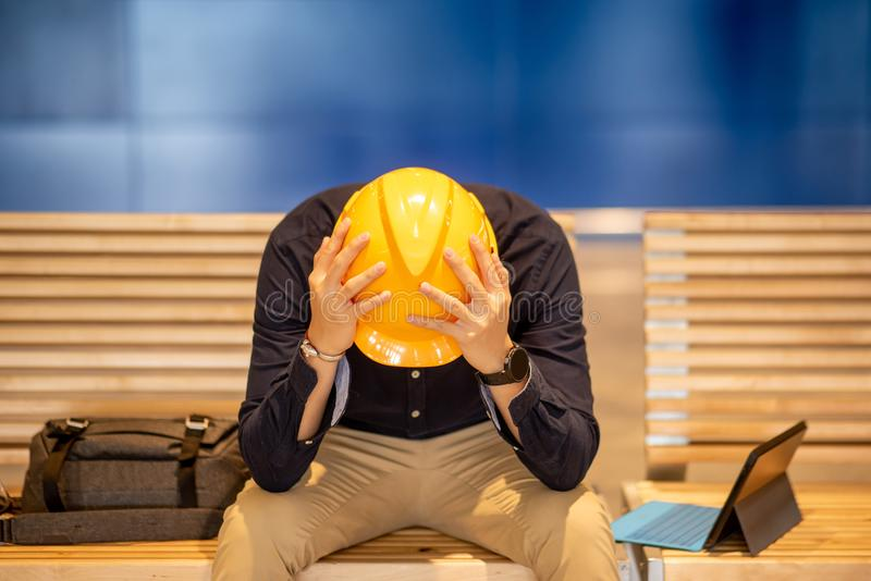 Young Asian engineer man feeling tried while sitting on bench. Young Asian engineer or architect man feeling tried and worried while sitting on bench holding his stock images