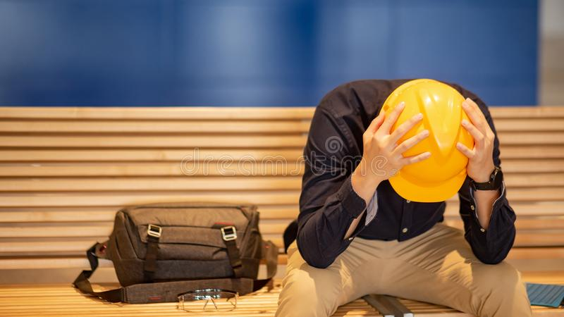 Asian engineer man feeling tried while sitting on bench. Young Asian engineer or architect man feeling tried and worried while sitting on bench holding his stock photos