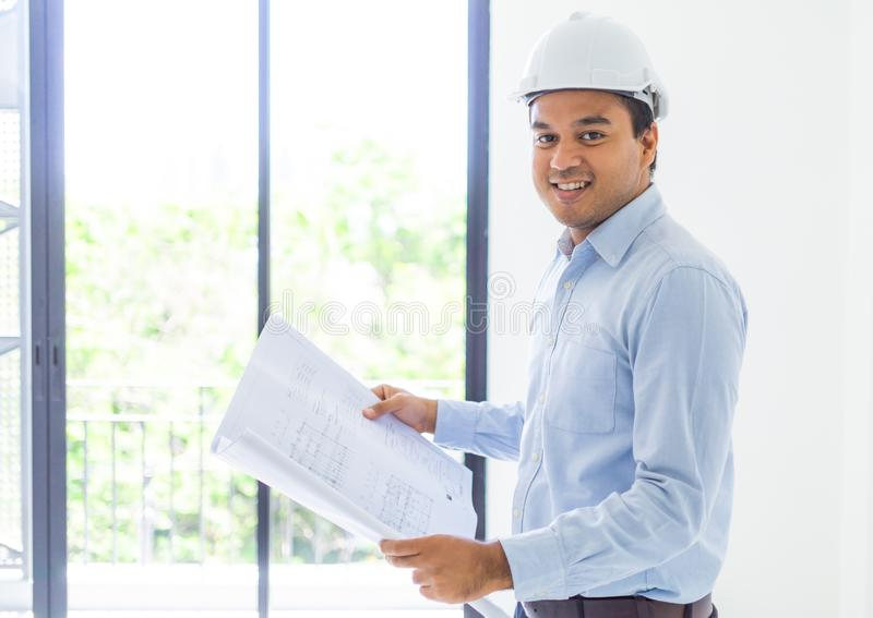 Young asian engineer or architects holding layout plan of building royalty free stock photography