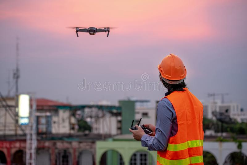 Young Asian engineer flying drone over construction site stock image