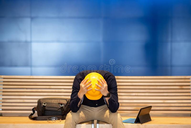 Young Asian engineer man feeling tried while sitting on bench. Young Asian engineer or architect man feeling tried and worried while sitting on bench holding his stock image