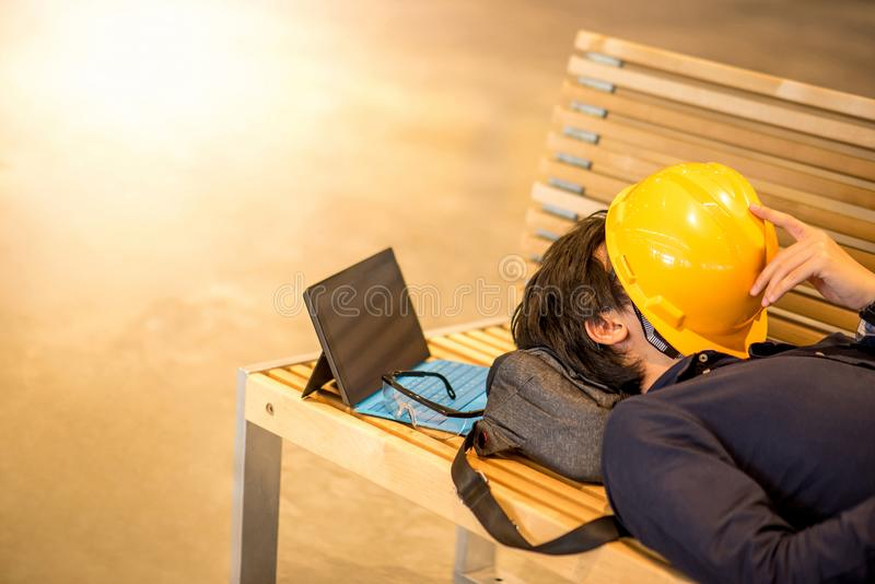 Young Asian engineer man lying on bench feeling tried stock photography