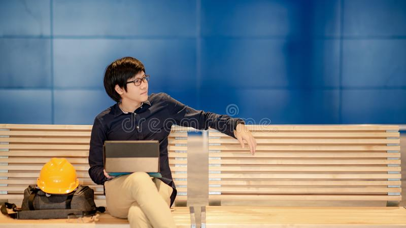 Asian engineer man using digital tablet on bench. Young Asian engineer man using digital tablet while sitting with personal yellow protective safety helmet and stock image