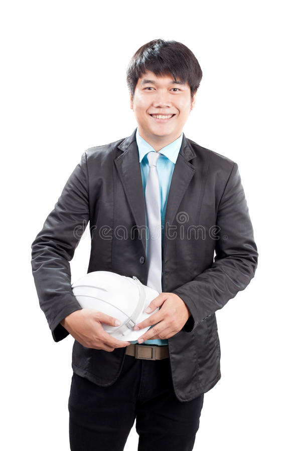 Young asian engineering man standing and holding safety helmet i royalty free stock image