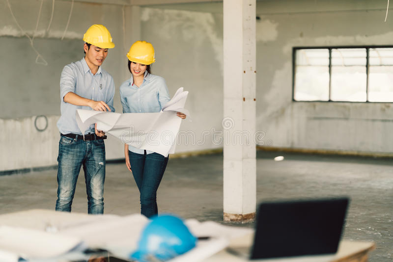 Young Asian engineers couple working on building blueprint at construction site. Civil engineering, industrial, or home renovation stock photography