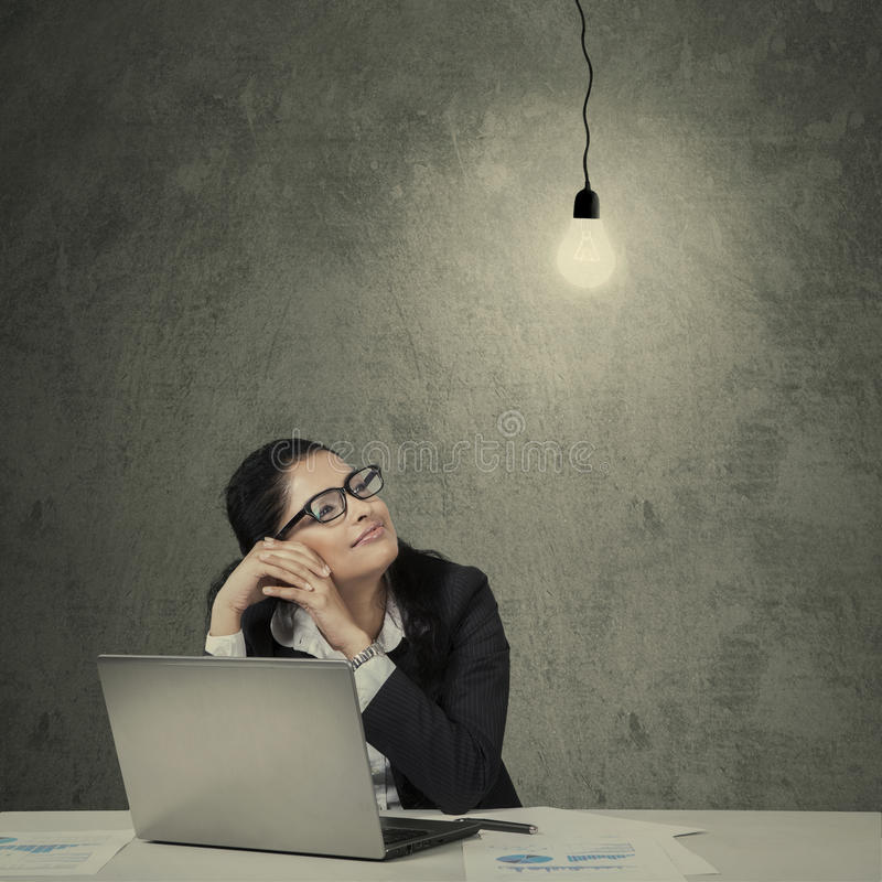 Young asian entrepreneur looking at lamp. Female asian manager working on desk with laptop and paperwork looking at bright lightbulb stock images