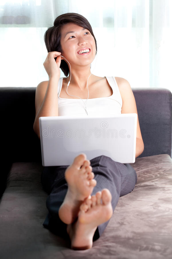 Young Asian executive relaxing on couch listening stock image