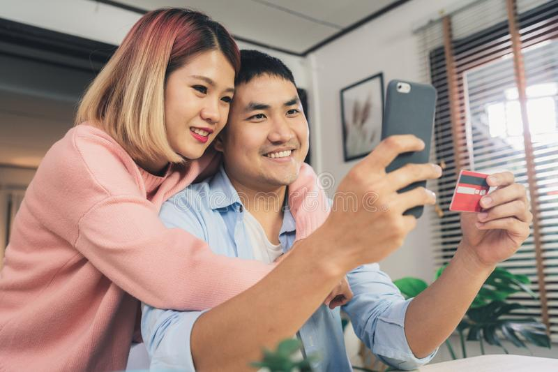Asian family couple using smartphone discussing news or doing online shopping sitting together on desk at home. royalty free stock photos