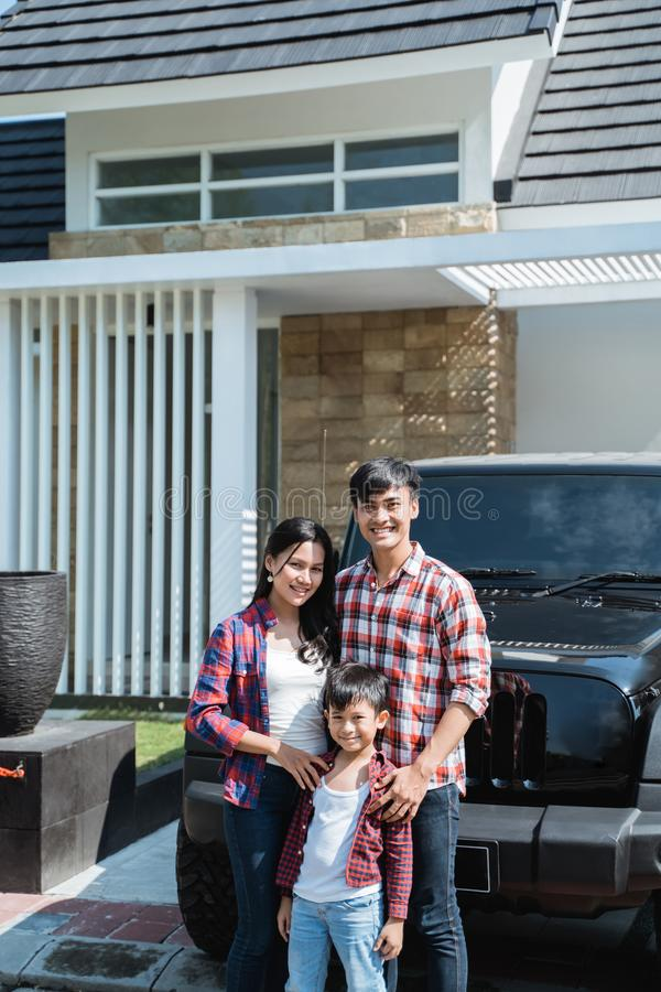 Asian family with kid in front of their house and car stock photography