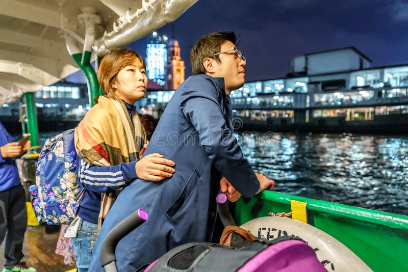 Young Asian family passing Victoria Harbor on Star Ferry boat at dusk on city lights stock photos