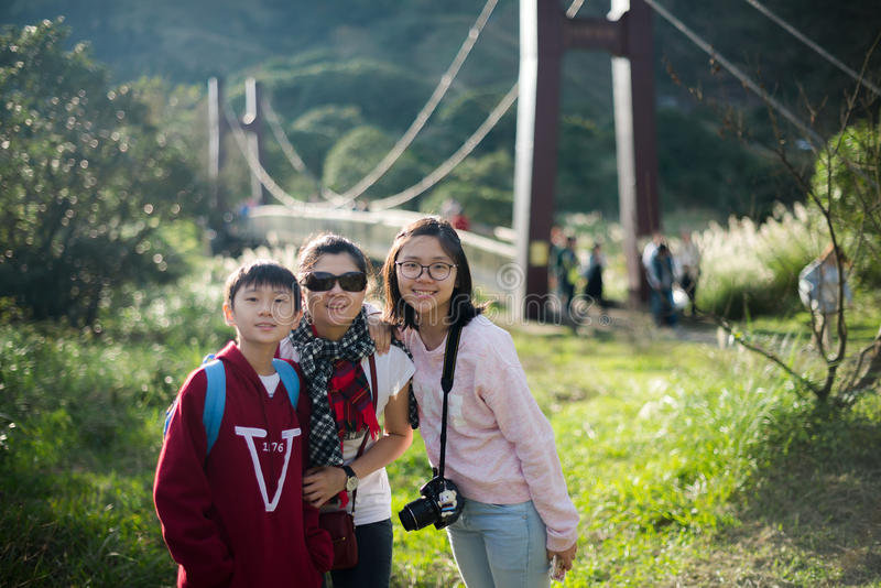 Young Asian family pose beside suspension bridge with backlit stock photos