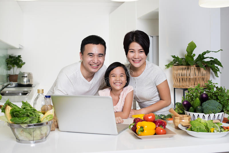 Young Asian family using the computer together at home. royalty free stock photos