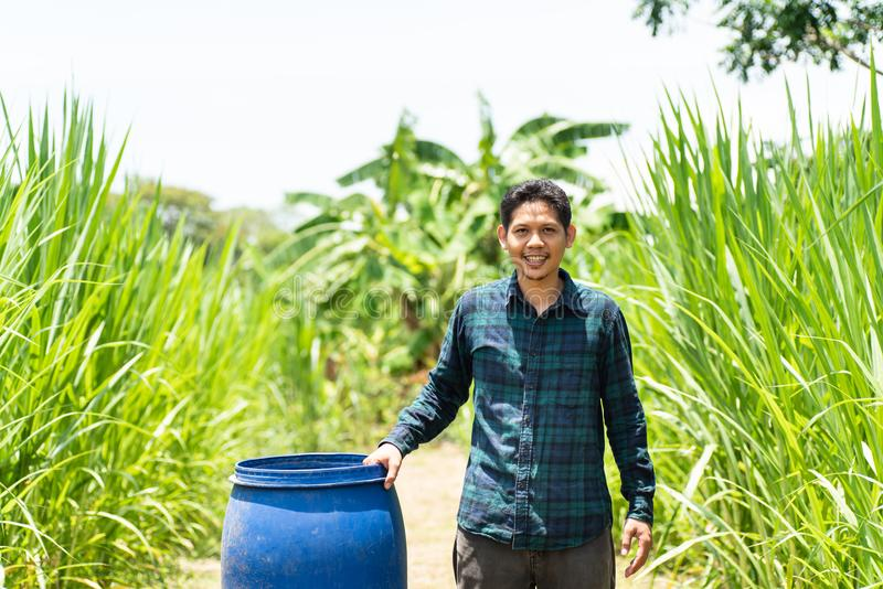 Young Asian farmer standing with blue water tank royalty free stock photos