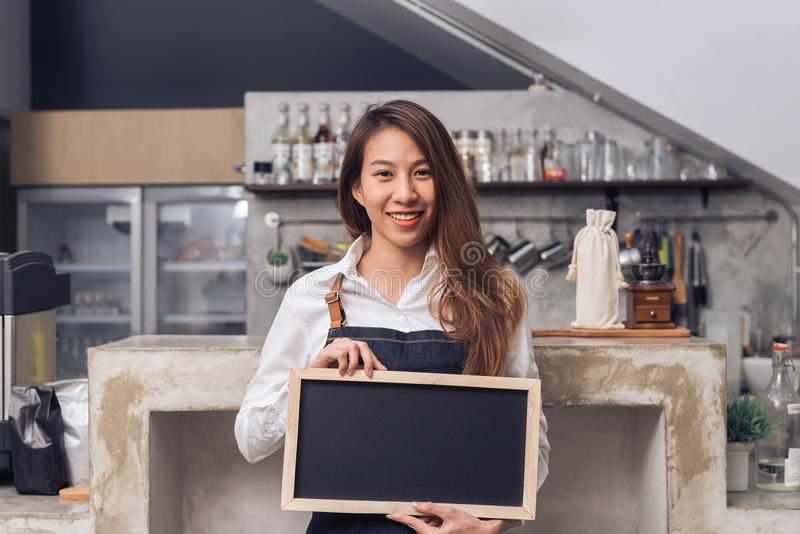 Young Asian female barista in denim apron hold a chalkboard with a beautiful smile in her own coffee shop welcome. Young Asian female barista in denim apron stock photography