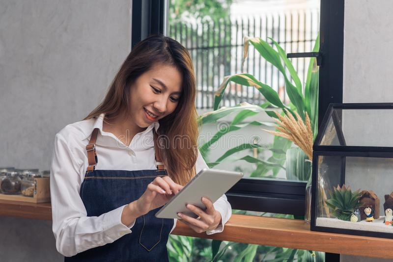 Young Asian female barista using electronic tablet in her own coffee shop while takeing break in warm afternoon. Young female barista and her modern small stock photos