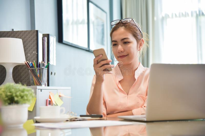 Young Asian Female creative designer using cell phone. Young Asian Female creative designer using cell phone at her workplace. A Woman doing Online shopping stock photos