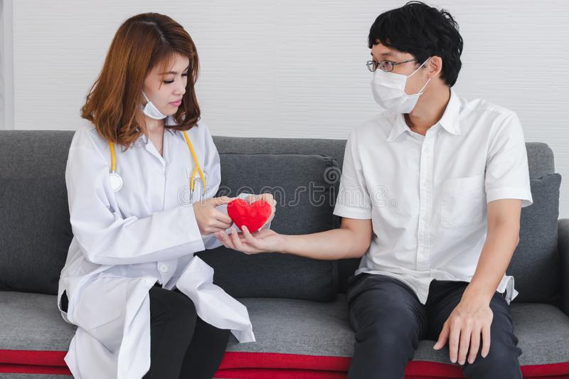 Young Asian female doctor giving red heart patient for encouragement and empathy stock photography