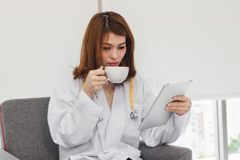 Young Asian female doctor looking tablet between break in hospital office.  royalty free stock images