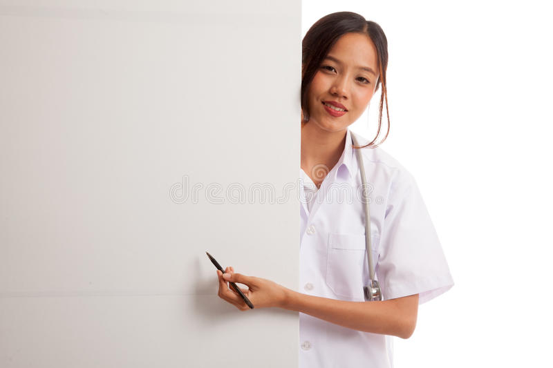 Young Asian female doctor peeking from behind blank sign point w stock photo