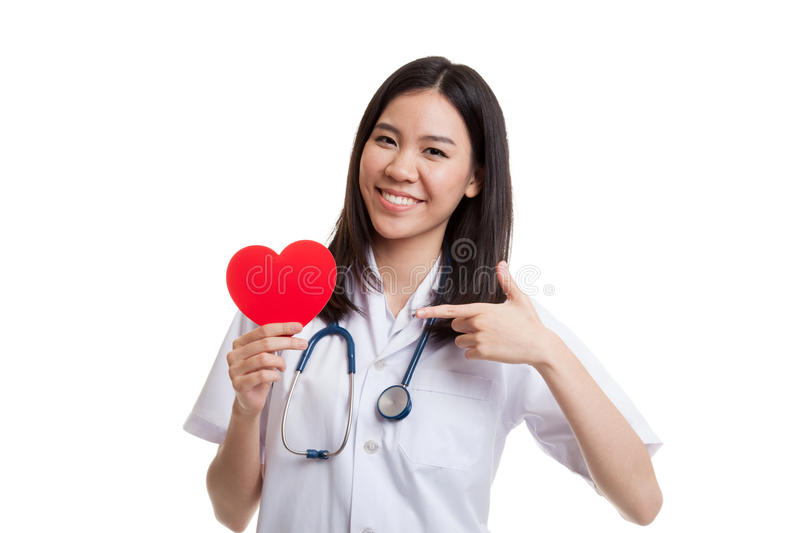 Young Asian female doctor point to red heart. Young Asian female doctor point to red heart isolated on white background royalty free stock photography