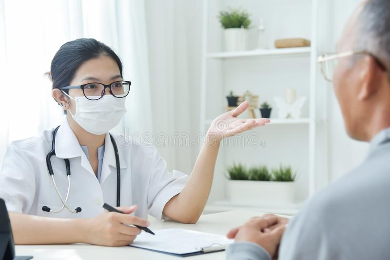 Asian Female Doctor talking to senior man patient. royalty free stock photo