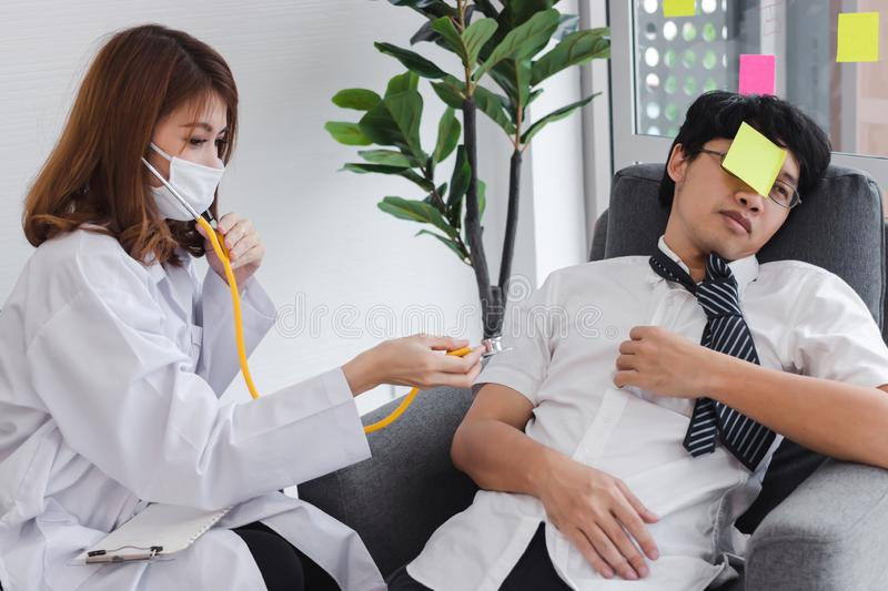 Young Asian female doctor with stethoscope diagnosing disabled business man stock photography