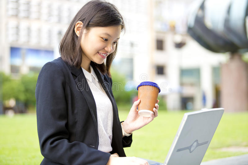Young Asian female executive drinking coffee and using laptop PC. Smiling royalty free stock image