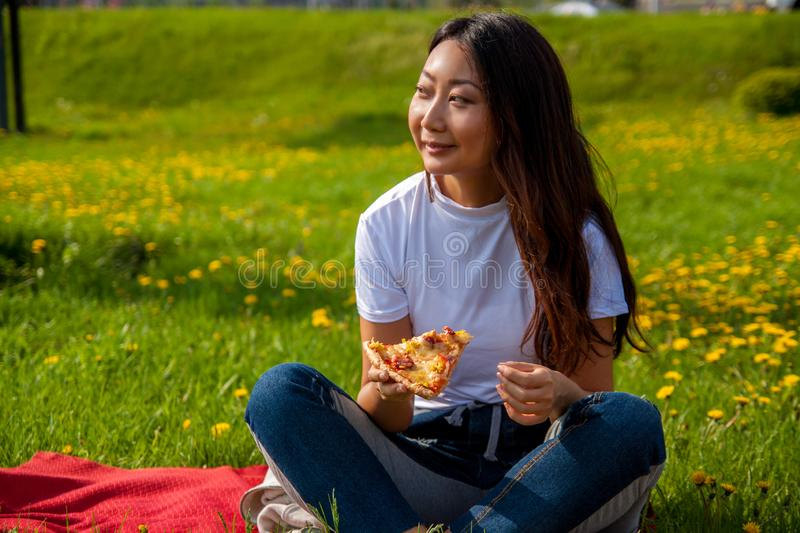 Young female with long hair holding slice of pizza while sitting on grass and enjoying lunch. Young asian female with long hair holding slice of pizza while royalty free stock photography