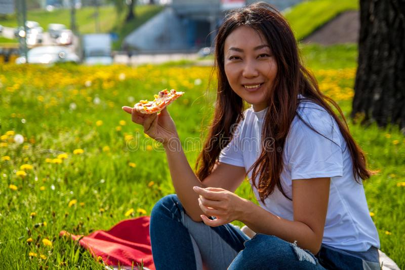 Young female with long hair holding slice of pizza while sitting on grass and enjoying lunch. Young asian female with long hair holding slice of pizza while royalty free stock images