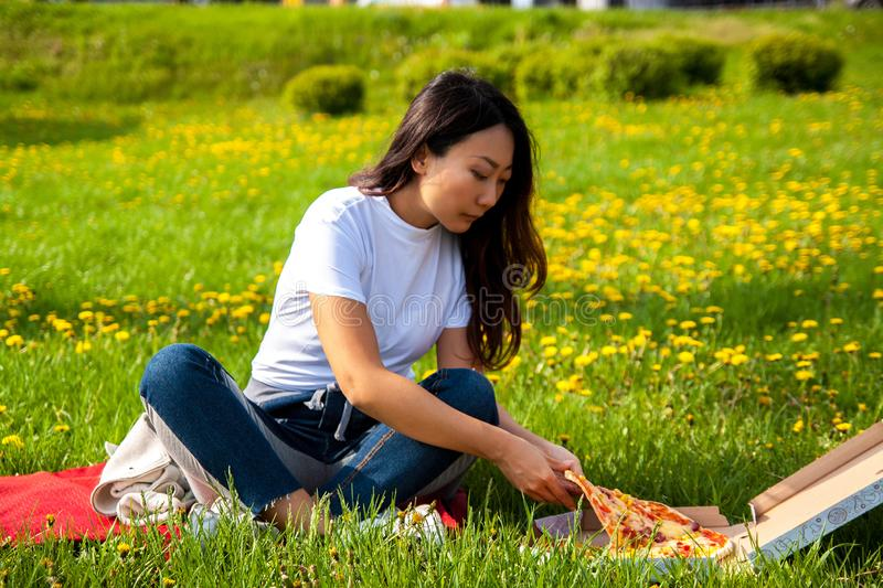 Young female with long hair holding slice of pizza while sitting on grass and enjoying lunch. Young asian female with long hair holding slice of pizza while stock photos