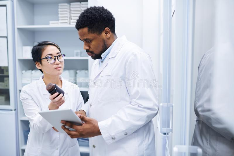 Medical assistant asking doctor about pills royalty free stock image