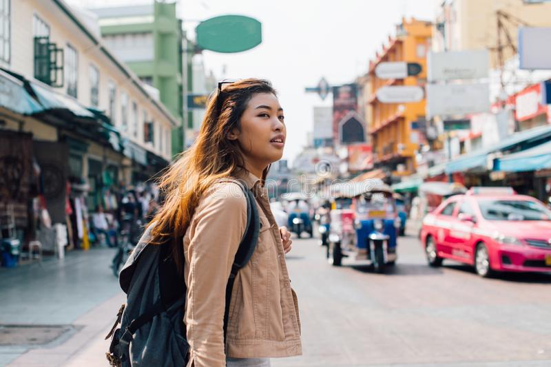 Young Asian female tourist backpacker walking on Khao San road during traveling to Thailand stock photography