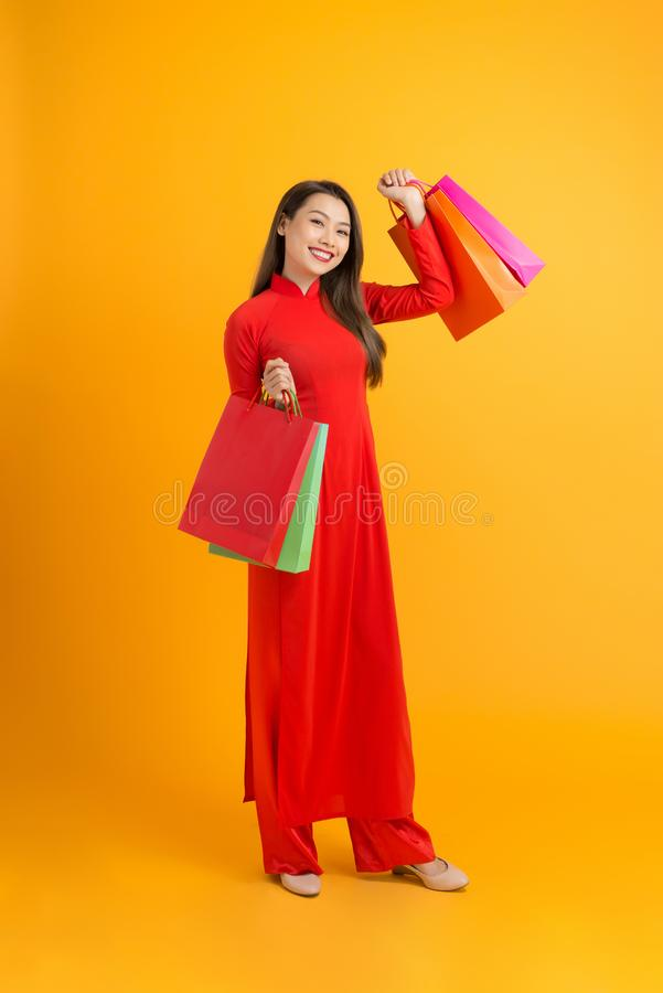 Young Asian female in traditional ao dai dress shopping, hand holding paper bag, celebrating Lunar New Year or spring festival.  stock photos