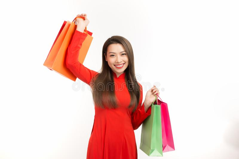 Young Asian female in traditional ao dai dress shopping, hand holding paper bag, celebrating Lunar New Year or spring festival.  royalty free stock photo
