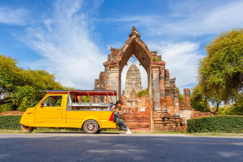 Young asian female traveler with backpack traveling sitting on taxi or Tuk Tuk and see map travel with old temple Wat Mahathat b stock photography