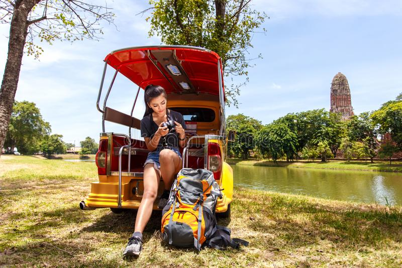 Young asian female traveler with backpack traveling sitting on taxi or Tuk Tuk and seeing photo on vintage camera with Wat Mahatha stock photo