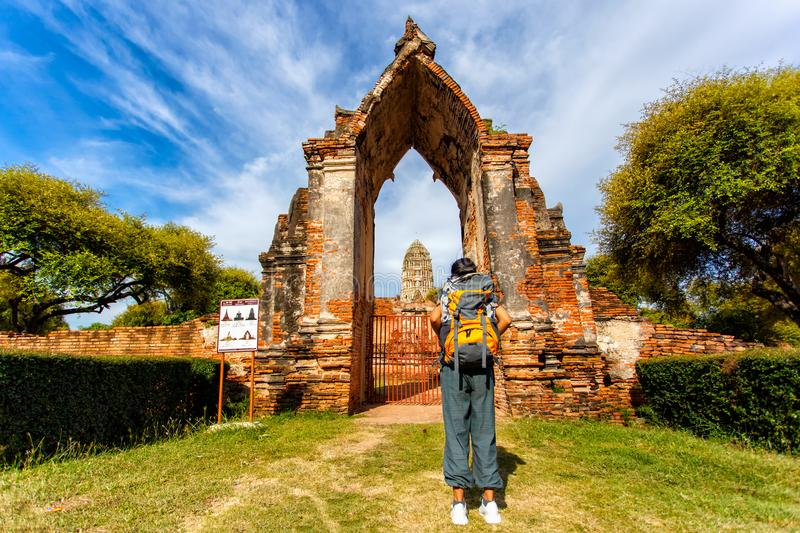 Young asian female traveler with backpack traveling with standing look at view with old temple Wat Mahathat, Ayutthaya Province royalty free stock images