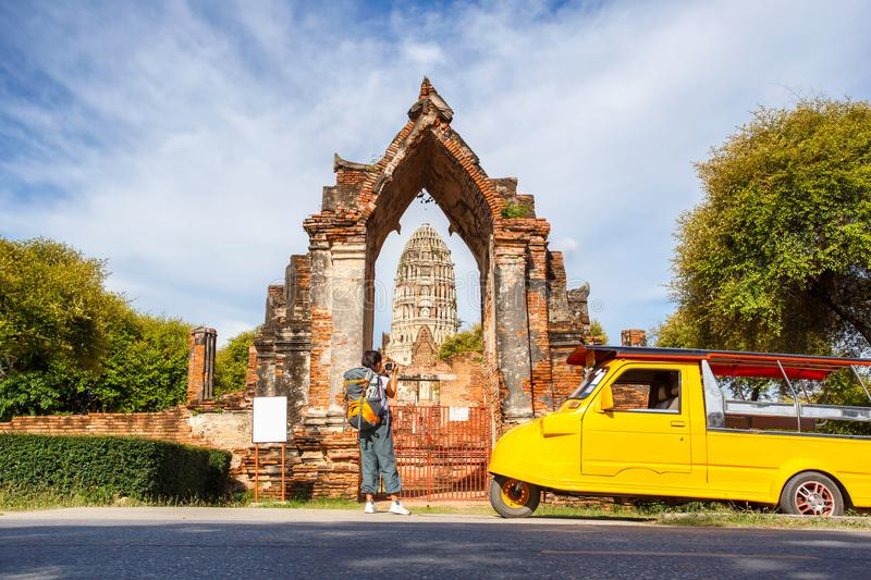 Young asian female traveler with backpack traveling and take a photo on vintage camera with Wat Mahathat background, Ayutthaya Pro royalty free stock photo