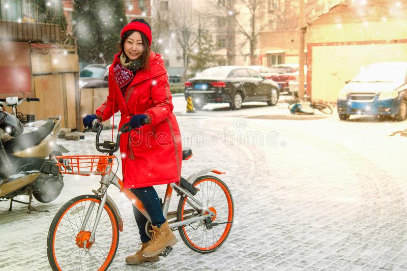 Young Asian girl on a bike in winter in the yard. royalty free stock photos