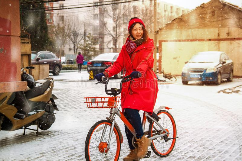 Young Asian girl on a bike in winter in the yard. royalty free stock photo
