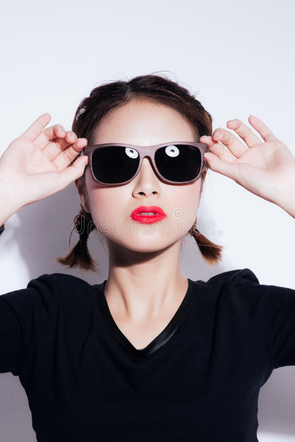 Young asian girl doing emotion. Dressed in a black shirt and yellow skirt, glasses and bright lips,trendy clothes. stock photography