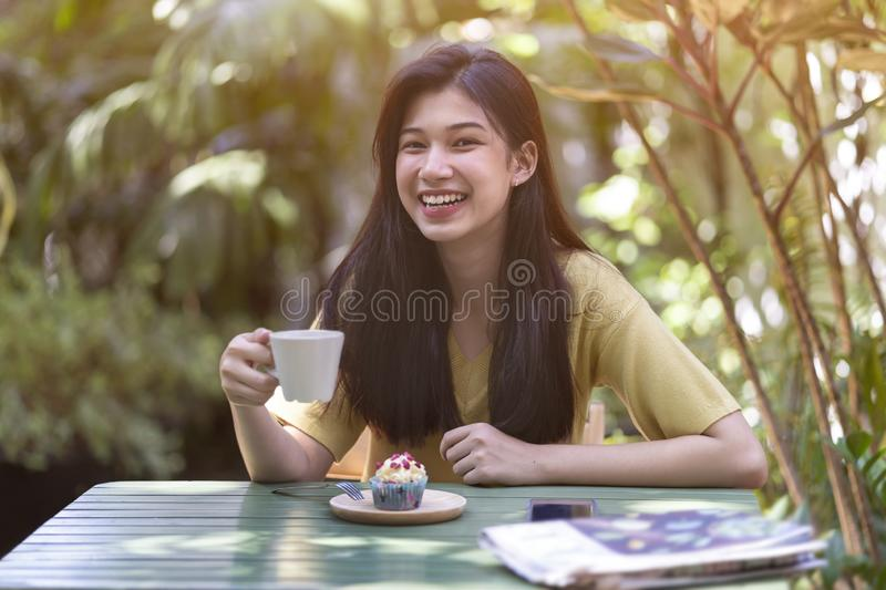 Young asian girl drinking hot coffee with eat cupcake in the garden stock photo