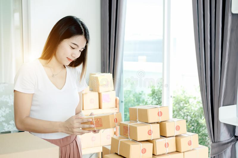 Young asian girl is freelancer with her private business. At home office, working with laptop, coffee, online marketing, Customer order and packaging or packing royalty free stock images