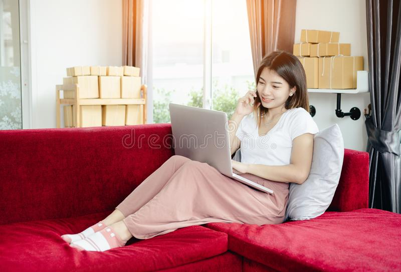 Young asian girl is freelancer. With her private business at home office, working with laptop, coffee, online marketing, Customer order and packaging or packing royalty free stock photos