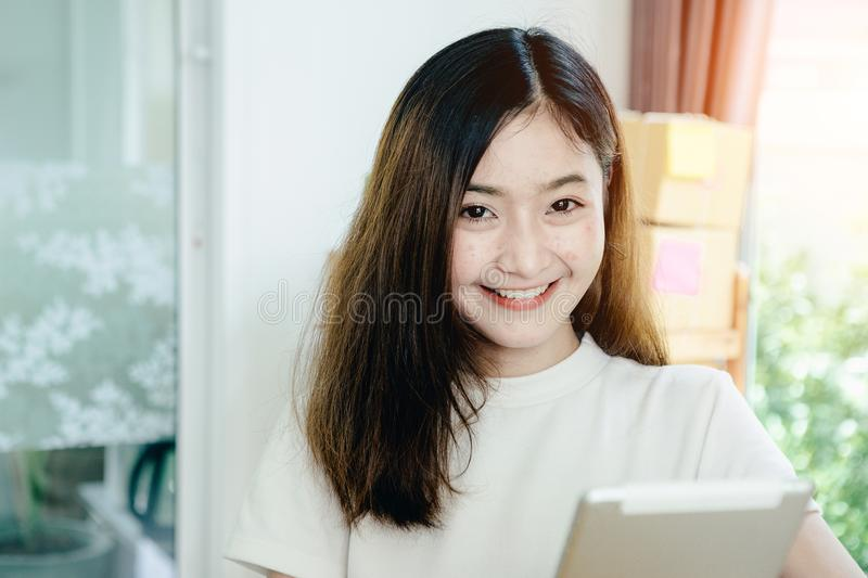 Young asian girl is freelancer with her private business. At home office, working with laptop, coffee, online marketing, Customer order and packaging or packing stock photo